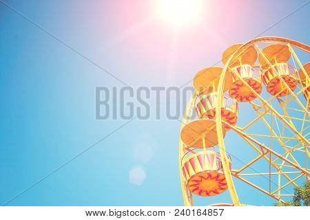Bright Ferris Wheel Against The Blue Sky With A Sunlight Glare. Space For Text