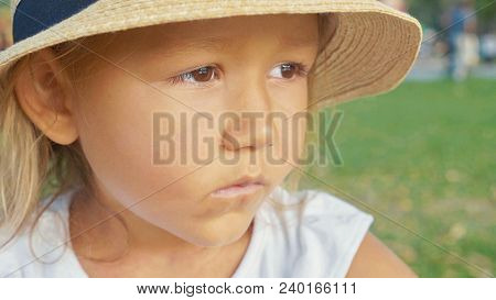 Close-up Portrait Of Beautiful Cute Seriously Little Girl In Coutry Style Hat.