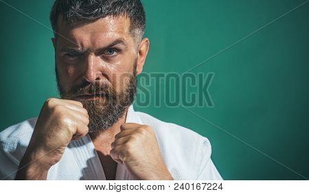 Karate Man In Kimono In Fighting Stance On Green Background. Closeup Of Male Karate Fighter Hands. P