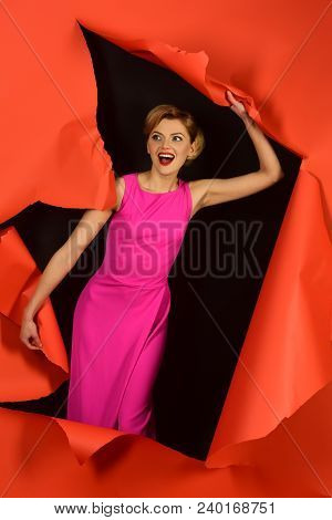 Pretty Blonde Girl In Pink Dress With Glamour Makeup, Red Lips Comes Out Through Gap In Red Paper. B