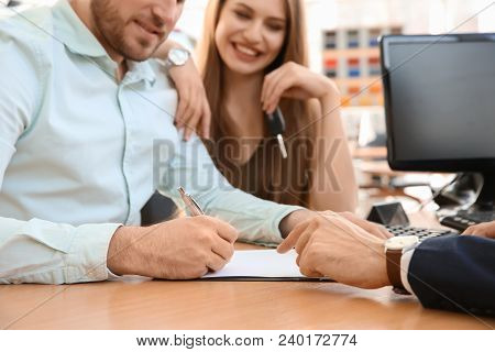 Young Couple And Salesman Sitting At Table In Car Salon. Buying Auto