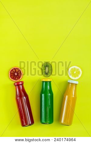 Beautiful Food Art Background. Yellow, Red And Green Juices In Glass Bottles Sliced Lemon, Kiwi And