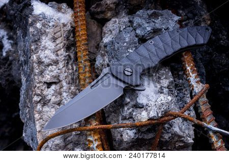 Folding knife with flipper. Knife on the background of concrete and reinforcement. poster