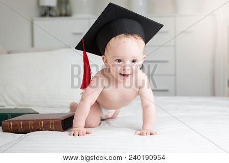 Funny Photo Of Adorable Baby Boy In Diapers Wearing Graduation Cap Crawling On Bed