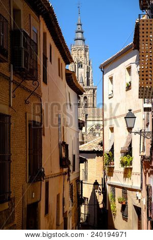 Narrow alley on the historic city of Toledo in Spain with a view of the cathedral