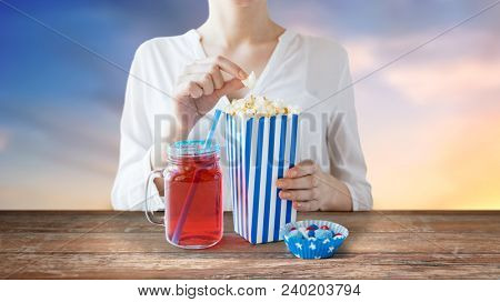 american independence day, celebration, patriotism and holidays concept - close up of woman eating popcorn with drink in glass mason jar and candies at 4th july party over evening sky background