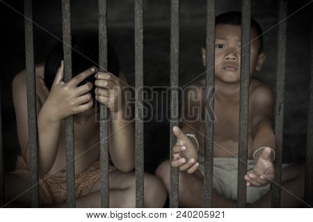 Two Children Hold Cage With Sad And Hopeless,victims Of Human Trafficking,violence Against Children