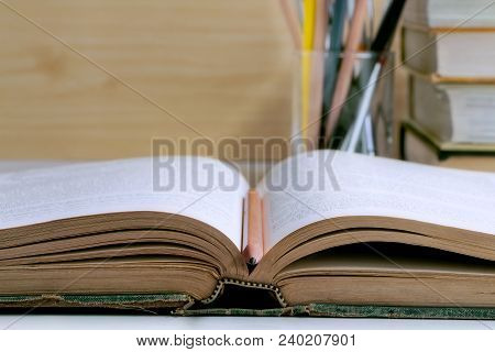 Open Hardback And Textbook Stacked On The Table Background. The Concept Of Intelligence Comes From E