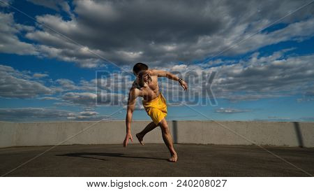 Tricking On Street. Martial Arts. Man Performs Leap With Support Of His Hand Barefoot. Shooted From