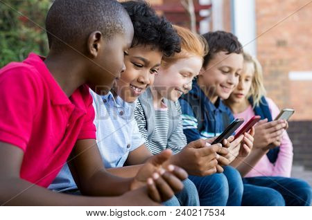 Pupils using mobile phone at the elementary school during recreation time. Group of multiethnic children sitting in a row and typing a message on smartphone. Young boys and girls with cellphone.