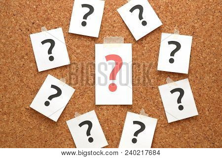 Red Question Mark On A Piece Of Paper And Many Question Marks On Cork Board. Question Concept.