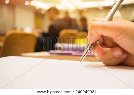 Business Concept : Hand Businessman Holding Silver Pen To Taking Notes On White Paperwork Or Documen