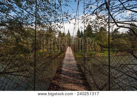 Old Hanging Wooden Bridge Over River Vah On Summer Day