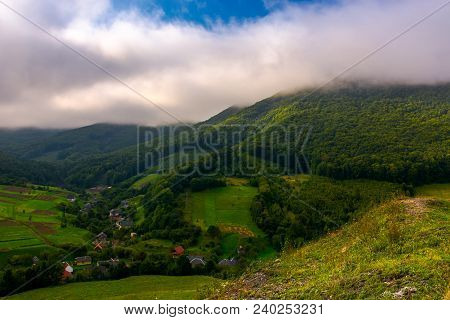 Small Carpathian Village In Mountains. Beautiful Landscape With Forested Hills And Agricultural Fiel
