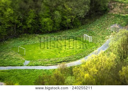Small Football Pitch In A Park Seen From Above With Two Goals Surround By Trees