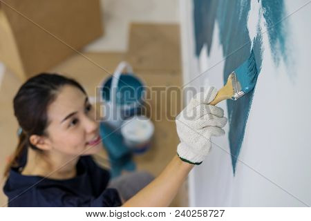 Young Asian Couple Painting Interior Wall With Paint Brush In New House