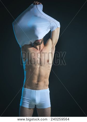 Handsome Man, Muscular Macho, Bodybuilder, With Sexy, Muscle Torso, Removes T-shirt. Attractive Man