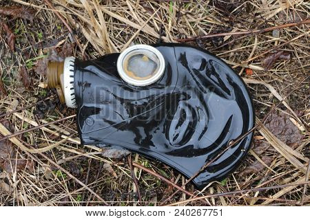 old gas mask lies on  wilted grass after rain. concept: biological and gas danger,  end of  world, Apocalypse, death, war. poster