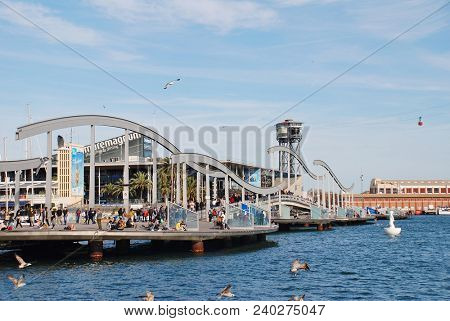 BARCELONA, SPAIN - APRIL 15, 2018: People cross the Rambla del Mar floating footbridge at Port Vell. Leading to the Moll d'Espanya, the bridge was completed in 1994.