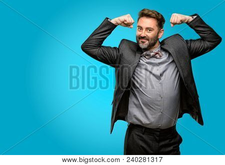 Middle age man, with beard and bow tie showing biceps expressing strength and gym concept, healthy life its good