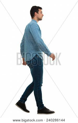 Full Length Profile Shot Of A Young Confident Man Walking Isolated On White Background