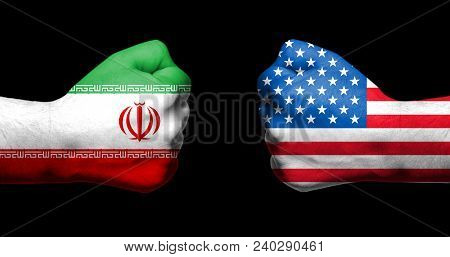 Flags Of Usa And Iran Painted On Two Clenched Fists Facing Each Other On Black Background/tensed Rel