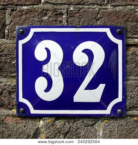 House Number Thirty Two  - 32 Against A Brick Wall