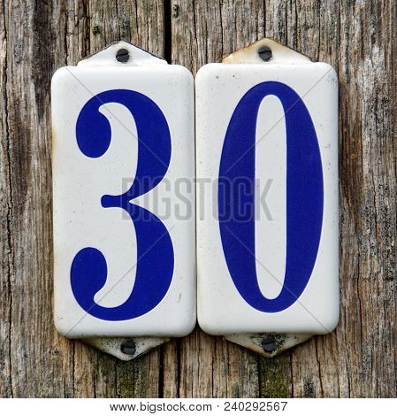 House Number Thirty  - 30 - Against A Wooden Background