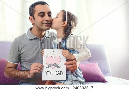 Happy Father's Day Portrait. Child Daughter Kissing Her Smiling Dad And Congratulating Him With A Po