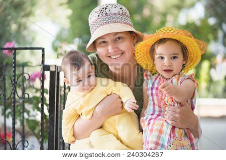 Mother, Little Daughter And Baby Son Portrait Outdoors In Summer