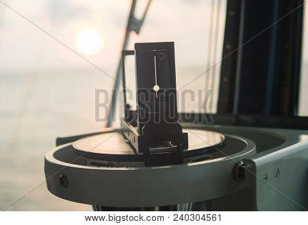 Close Up Of Nautical Marine Magnetic Compass On Yacht Or Boat With Beautiful Sunrise On Background.