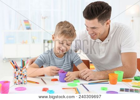 Young man and little boy playing together indoors. Child adoption