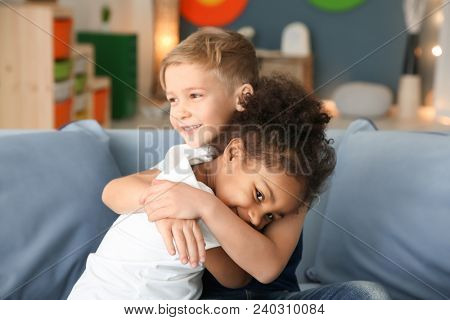 Cute boy and African-American girl indoors. Child adoption
