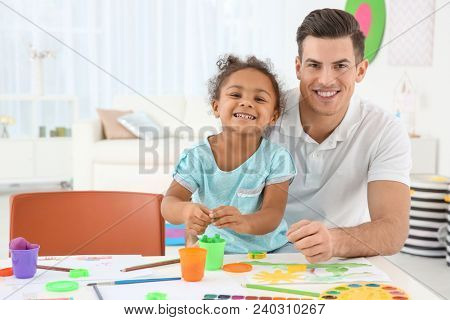 Young man and little African-American girl playing together indoors. Child adoption