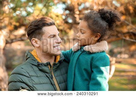 Young man and little African-American girl outdoors on sunny day. Child adoption