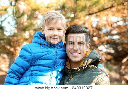 Young man and little boy outdoors on sunny day. Child adoption