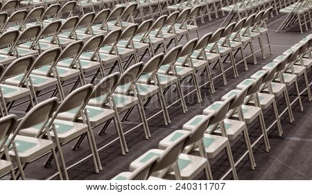 Symmetrical Rows Of Silver Folding Chairs With A Green Folder Placed On The Seat Of Each One