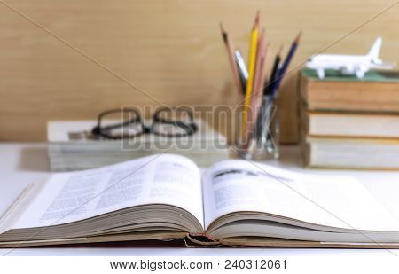 Open Hardback Or Textbook With Glasses, And Stationary Placed On The Table. The Concept Of Intellige