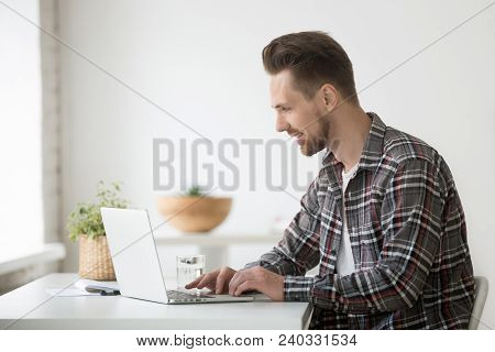 Smiling Man Freelancer Working On Laptop Sitting At Home Office Desk, Happy Casual Young Businessman