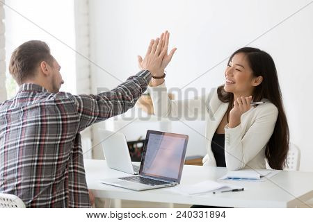 Young Asian And Caucasian Partners Giving High Five At Workplace, Diverse Motivated Colleagues Celeb