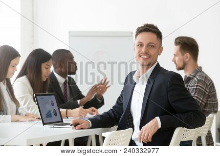 Smiling Young Businessman In Suit Looking At Camera Posing With Laptop At Group Meeting, Happy Proje