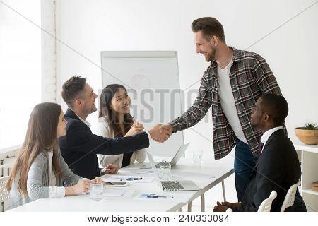 Smiling Businessman Handshaking Welcoming New Member At Multiracial Team Meeting, Friendly Partners