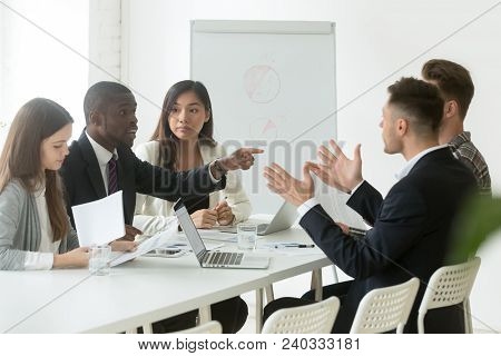 Diverse Employees Arguing During Team Meeting, African Office Worker Disagreeing With Caucasian Coll