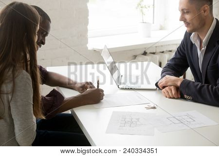 Interracial Couple Signing Mortgage Investment Contract Making Real Estate Deal At Meeting With Brok