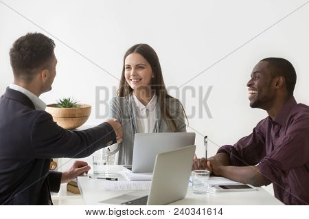 Smiling Millennial Businesswoman Shaking Hand Of Male Partner At Diverse Group Negotiation, Friendly