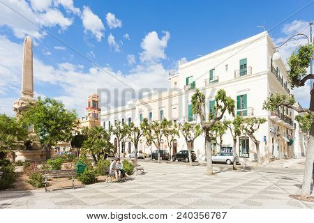 Gallipoli, Apulia, Italy - May 2017 - People On A Bench At The Obelisk Square Of Gallipoli