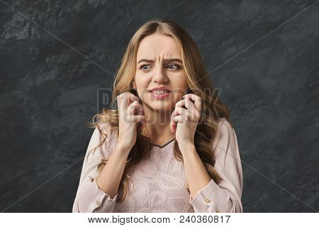 Portrait Of Afraid Young Woman. Scared Girl Grimacing And Gesturing On Gray Studio Background