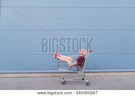 Happy Girl Sits In A Cart For Shopping On The Background Of A Blue Wall. Street Fashion. Girl Hipste