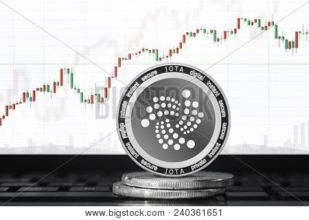 Iota (iot) Cryptocurrency; Physical Concept Iota Coin On The Background Of The Chart