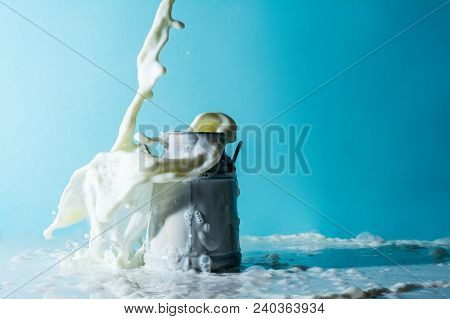 Splash of milk, stream of milk pouring into a overflowing can of milk on a light blue celestial sky background poster